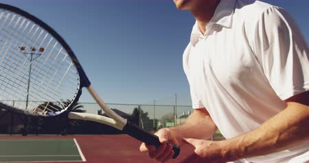 tennis whites : Side view close up of a young Caucasian man playing tennis on a court, waiting for the ball Stock Footage