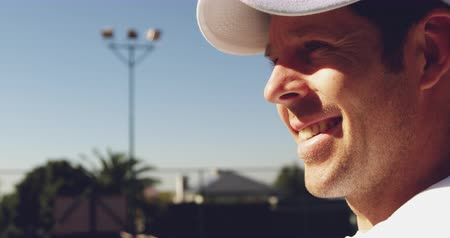 tennis whites : Close up side view of a young Caucasian man smiling during a tennis game on a sunny day