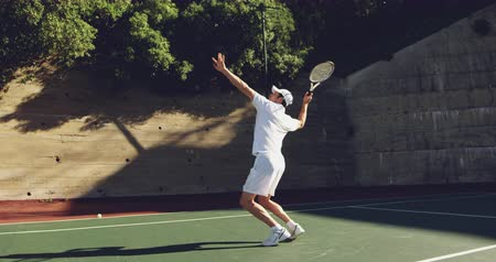 tennis whites : Side view of a young Caucasian man playing tennis on a sunny day, returning a ball Stock Footage