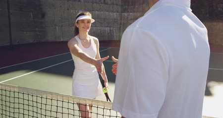 tennis whites : Front view close up of a young Caucasian woman and a young Caucasian man playing tennis on a court, shaking hands after a game