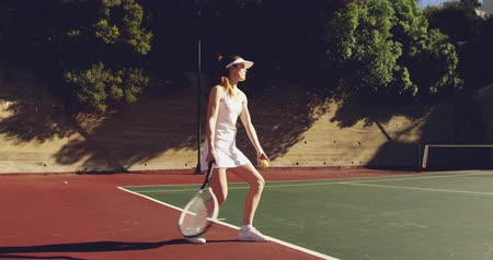 tennis whites : Side view of a young Caucasian woman and a young Caucasian man playing tennis on a court, woman bouncing a ball and serving