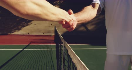 tennis whites : Close up mid section of a young Caucasian woman and a young Caucasian man playing tennis on a court, shaking hands after a game Stock Footage