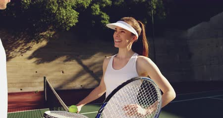 tennis whites : Side view close up of a young Caucasian woman and a young Caucasian man playing tennis on a court, talking over the net