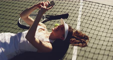 beyazlar : High angle side view of a young Caucasian woman taking a selfie during a break in a game of tennis, lying on the ground Stok Video