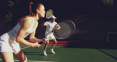 beyazlar : Side view of a young Caucasian woman and a young Caucasian man playing tennis on a court, man returning a ball