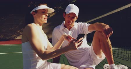 tennis whites : Front view close up of a young Caucasian woman and a young Caucasian man using a smartphone and talking during a break in a game of tennis