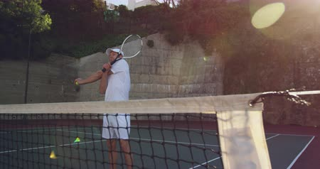 tennis whites : Front view of a young Caucasian man playing tennis on a court, stretching before a game Stock Footage