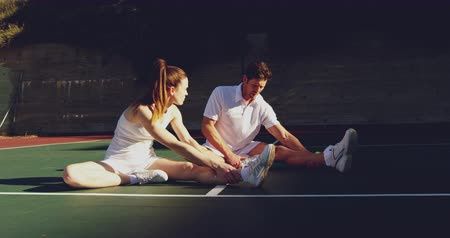 teniszütő : Front view of a young Caucasian woman and a young Caucasian man playing tennis on a court, stretching and talking before a game