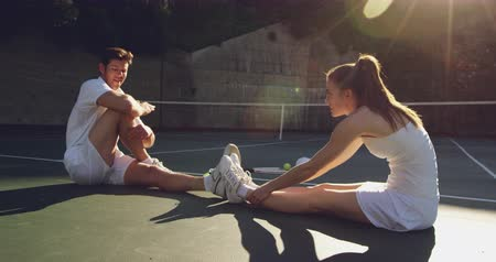 beyazlar : Side view of a young Caucasian woman and a young Caucasian man playing tennis on a court, stretching and talking before a game Stok Video