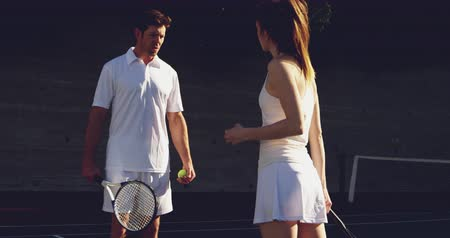 tennis whites : Front view of a young Caucasian woman and a young Caucasian man playing tennis on a court, bouncing a ball and talking