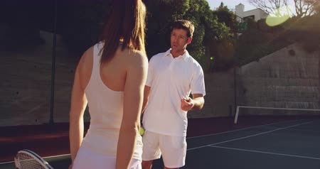tennis whites : Rear view of a young Caucasian woman and a young Caucasian man playing tennis on a court, talking