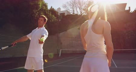 tennis whites : Rear view close up of a young Caucasian woman and a young Caucasian man playing tennis on a court, man giving instructions to the woman