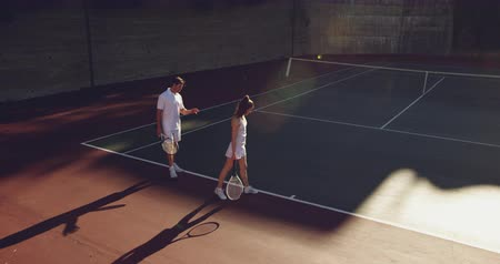 tennis whites : High angle side view of a young Caucasian woman and a young Caucasian man playing tennis on a court, man giving instructions to the woman Stock Footage