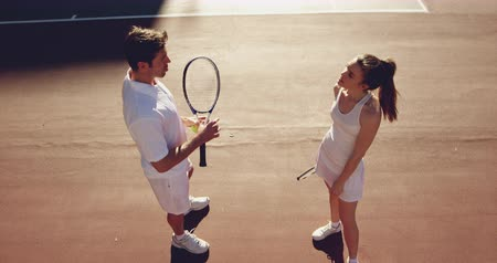 beyazlar : High angle side view of a young Caucasian woman and a young Caucasian man playing tennis on a court, bouncing a ball and talking