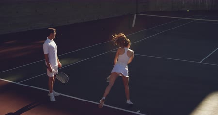 tennis whites : High angle rear view of a young Caucasian woman and a young Caucasian man playing tennis on a court, woman serving Stock Footage