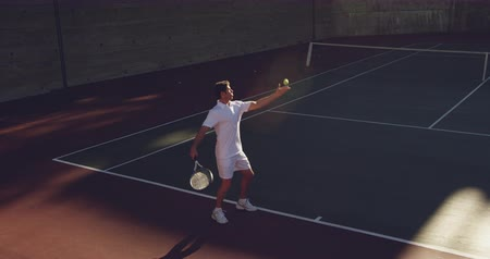 служить : High angle side view of a young Caucasian man playing tennis on a court, serving