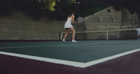 mulheres adultas meados : Rear view of a young Caucasian woman and a young Caucasian man playing tennis on a court, woman returning a ball