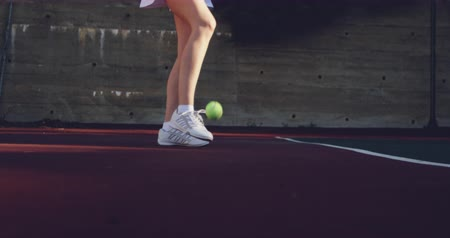sobressalente : Side view low section of a young Caucasian woman playing tennis on a court, preparing to serve