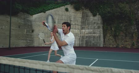 tennis whites : Front view of a young Caucasian woman and a young Caucasian man playing tennis on a court, man returning a ball