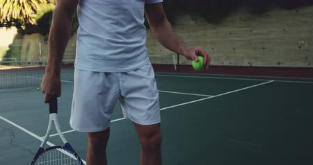 tennis whites : Front view mid section of a young Caucasian man playing tennis on a court, bouncing a tennis ball