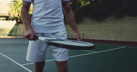 tennis whites : Front view mid section of a young Caucasian man playing tennis on a court, bouncing a tennis ball and a tennis racket