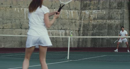 tennis whites : Rear view of a young Caucasian woman and a young Caucasian man playing tennis on a court, woman serving Stock Footage