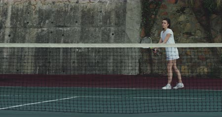 tennis whites : Front view of a young Caucasian woman playing tennis on a court, serving