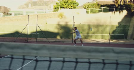 tennis whites : Front view of a young Caucasian man playing tennis on a court, returning a ball