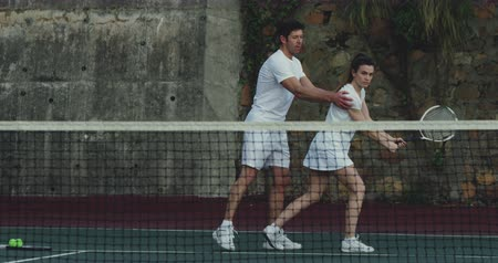 tennis whites : Side view of a young Caucasian woman and a young Caucasian man playing tennis on a court, man giving instructions to the woman