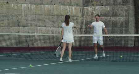tennis whites : Front view of a young Caucasian woman and a young Caucasian man playing tennis on a court, shaking hands over the net Stock Footage