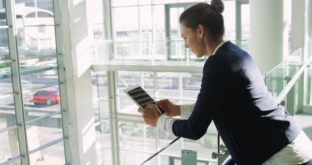 generation z : Side view close up of a young Caucasian businesswoman using a tablet computer standing leaning on a handrail in the sunny lobby of a modern office building, with traffic on the road outside