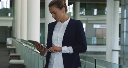 планшетный компьютер : Side view close up of a smiling young Caucasian businesswoman using a tablet computer standing in the lobby of a modern office building Стоковые видеозаписи