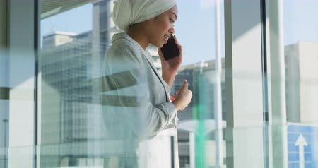 hijab : Side view close up of a smiling young mixed race businesswoman wearing a hijab talking on a smartphone standing in the sunny lobby of a modern office building, with modern office blocks in the background