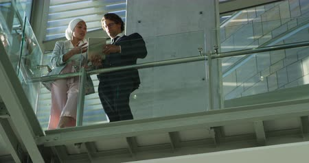 corrimão : Low angle view of a young mixed race businesswoman wearing a hijab talking with a young Caucasian businessman holding a tablet computer standing leaning on the handrail of a balcony in a sunny modern office building