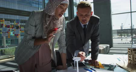 wind turbine : Front view close up of a young mixed race businesswoman wearing a hijab and a young Caucasian businessman standing at a table looking at a model wind turbine and talking during a meeting in a modern office