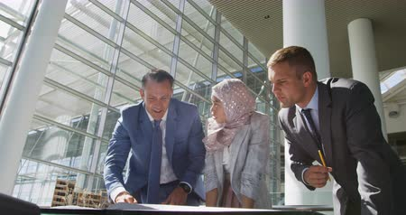 concentrando : Front view close up of a young mixed race businesswoman wearing a hijab, a young Caucasian businessman and a middle aged Caucasian businessman standing together and leaning over a table looking at documents and talking during a meeting in a modern office,
