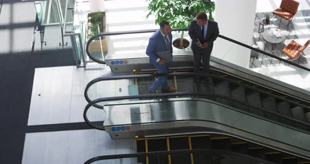 holding onto : High angle view of a young Caucasian businessman and a middle aged Caucasian businessman talking as they step onto and stand going down an escalator in a modern office building, one holding a laptop and one holding a tablet computer Stock Footage