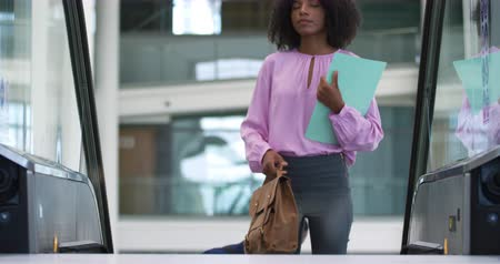 handbag : Front view of a young African American businesswoman holding a handbag and a file coming up on an escalator in the obby of a modern office building