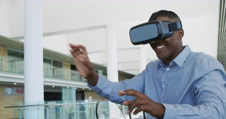generation z : Front view close up of a young African American businessman using a VR headset and gesturing with his hands in a modern office