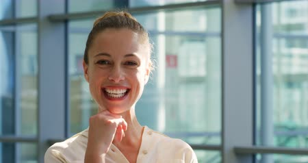 gülmek : Portrait close up of a young Caucasian businesswoman standing in the sunny lobby of a modern office building and smiling to camera Stok Video