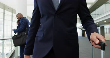 lobby : Front view close up of a young Caucasian businessman with a suitcase walking through the lobby of a modern office building with business people using smartphones in the background