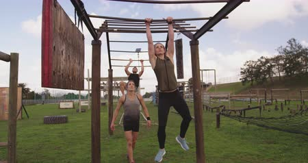 deneme : Front view of two young Caucasian women and a young Caucasian man using the monkey bars at an outdoor gym during a bootcamp training session Stok Video