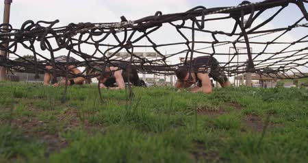 konkurenti : Front view of a young Caucasian man and two young Caucasian women crawling under a net at an outdoor gym during a bootcamp training session