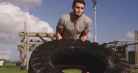 engel : Front view of a young Caucasian man flipping a tyre at an outdoor gym during a bootcamp training session