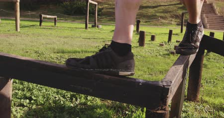 vyvažování : Side view low section of a young Caucasian man walking along a beam at an outdoor gym during a bootcamp training session