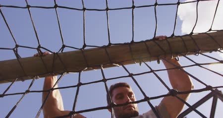 deneme : Front view of a young Caucasian man climbing over nets on a climbing frame at an outdoor gym during a bootcamp training session