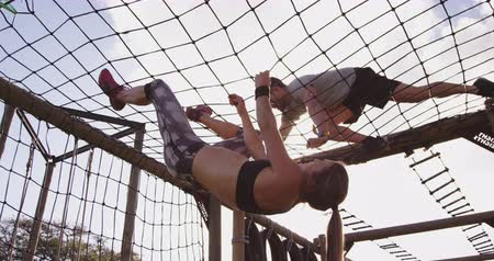 konkurenti : Side view of a young Caucasian woman and a young Caucasian man climbing on nets on a climbing frame at an outdoor gym during a bootcamp training session