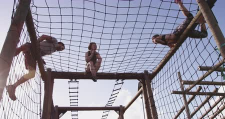 engel : Side view of a young Caucasian woman and a young Caucasian man climbing over nets on a climbing frame at an outdoor gym during a bootcamp training session, while another female participant sits on the frame clapping Stok Video