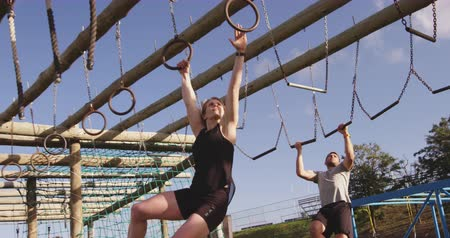 зависать : Front view of a young Caucasian woman and a young Caucasian man crossing a climbing frame hanging from rings and ropes at an outdoor gym during a bootcamp training session Стоковые видеозаписи