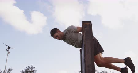 equipamentos esportivos : Side view of a young Caucasian man vaulting over a wall at an outdoor gym during a bootcamp training session